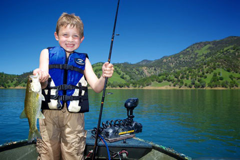 boy in boat holding up fish he caught